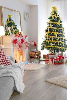 Interieur van mooie woonkamer met open haard versierd voor kerstmis