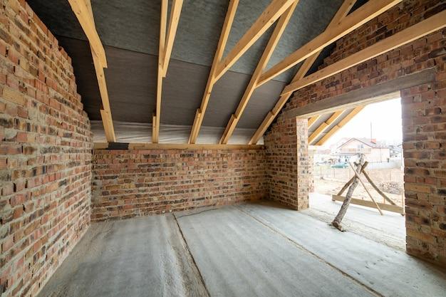 Interieur van onafgewerkt bakstenen huis met betonnen vloer, kale muren klaar voor pleisterwerk en houten dakframe zolder in aanbouw.