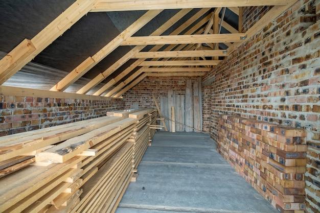 Interieur van onafgewerkte bakstenen huis met betonnen vloer, kale muren klaar voor pleisterwerk en houten dakframe zolder in aanbouw.