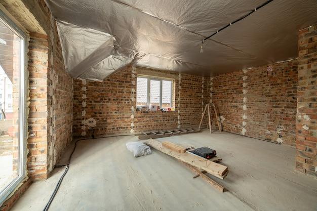 Interieur van onvoltooide bakstenen huis met betonnen vloer en kale muren klaar voor pleisterwerk in aanbouw. vastgoed ontwikkeling