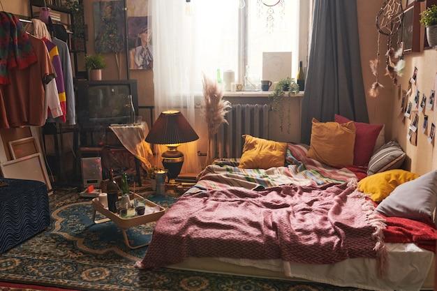 Interieur van ouderwetse huiskamer met kleren op het rek en dienblad met fles rode wijn op de vloer