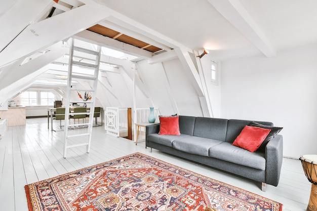 Interieur van ruime appartementkamer op zolder van gebouw ingericht met grijze bank en eettafel met ladder naar boven