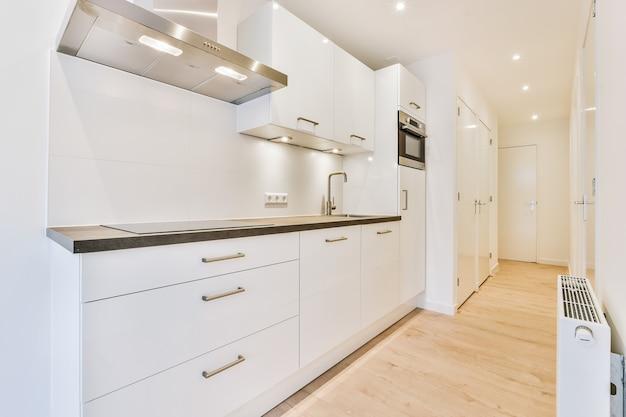Interieur van ruime keuken met witte kasten en glanzende inbouwapparatuur in nieuw appartement