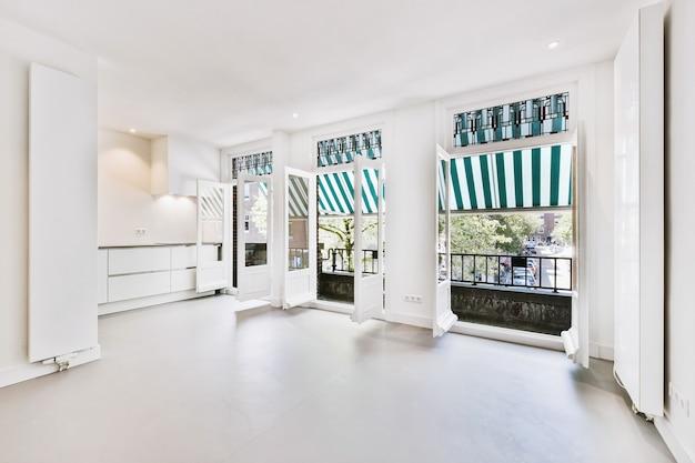 Interieur van ruime lichte kamer met openslaande deuren naar balkon met overkapping op zonnige zomerdag