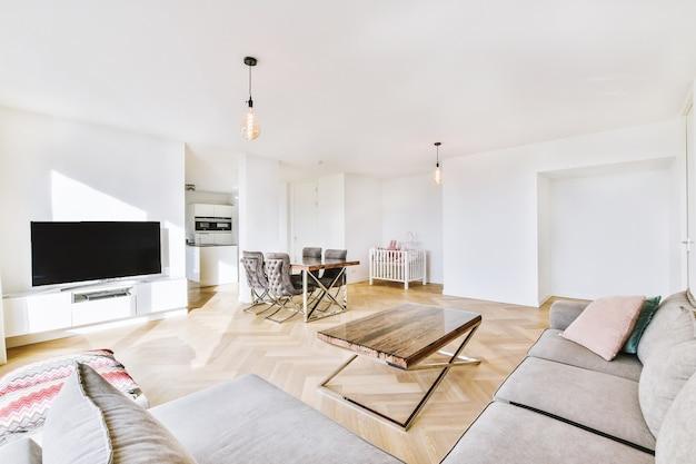 Interieur van ruime woonkamer met bank en moderne tv en eethoek in nieuwe flat