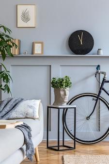 Interieur van scandinavische woonkamer met grijze bank, fotolijsten, planten, kussens, marmeren kruk, fiets en elegante persoonlijke accessoires in stijlvol interieur.