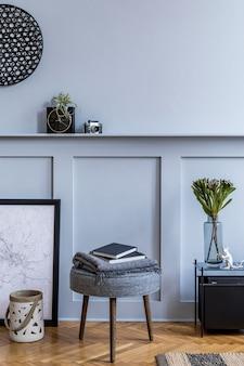 Interieur van scandinavische woonkamer met zwarte posterkaart, grijze kruk, zwarte salontafel, planten, bloemen in vaas, decoratie, tapijt, boek en elegante persoonlijke accessoires.