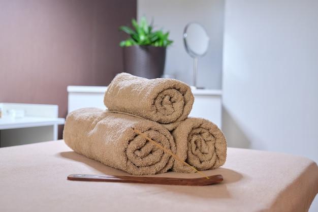 Interieur van spa-kast, massagetafel, handdoeken, cosmetica, massageoliën, aromasticks met rook