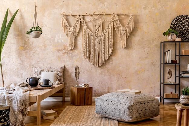 Interieur van stijlvolle woonkamer met chaise longue, mooie macrame, rotan decoratie, planten, boek, plant, elegante persoonlijke accessoires in oosters concept van home decor.