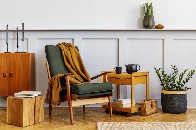 Interieur van stijlvolle woonkamer met vintage groene fauteuil, houten salontafel, meubels, grijze muur, plank, tapijt, planten, decor, boek, kopieerruimte en elegante persoonlijke accessoires.