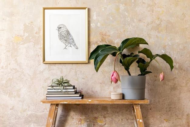Interieur van woonkamer met fotolijst, planten, houten bank, boeken, luchtplant en elegante persoonlijke accessoires in modern interieur.