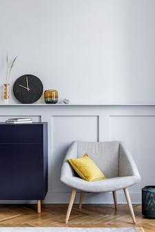 Interieur van woonkamer met stijlvolle marineblauwe commode, grijze fauteuil, kussen, zwarte klok, moderne schilderijen, decoratie en elegante accessoires in woondecoratie.