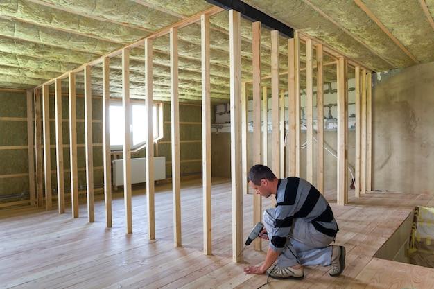 Interieur van zolder geïsoleerde kamer met eiken vloer in wederopbouw. jonge professionele werknemer gebruikt niveau en schroevendraaier houten frame installeren voor toekomstige muren. renovatie en verbetering concept.