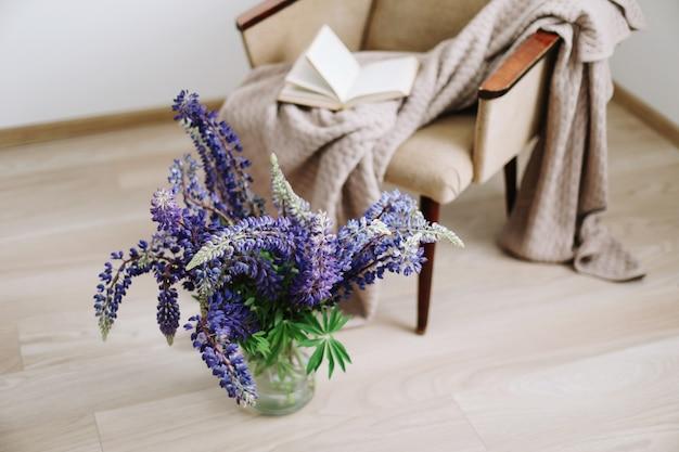 Interieur woondecoratie met bloemen en boeken boeket paarse lupines in een vaas