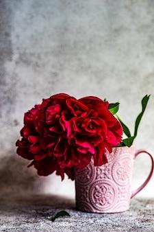 Interieurdecoratie met keramische vaas of beker met rode pioenbloemen