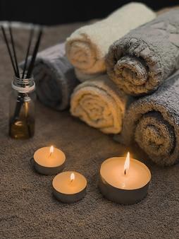 Interieurelementen voor comfort in een schoonheidsstudio. een aangename sfeer in de massageruimte. achtergrond voor een spa salon. aangestoken kaarsen, wierookstokjes, mooi opgevouwen handdoeken.
