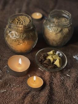 Interieurelementen voor comfort in een schoonheidsstudio. een aangename sfeer in de massageruimte. kuuroordachtergrond. aangestoken kaarsen, handdoek, potten met materiaal voor procedures