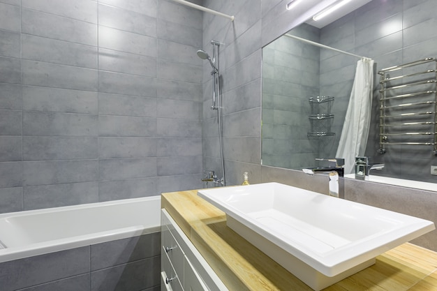 Interieurfoto van een moderne badkamer met grijze tegels in een klein appartement