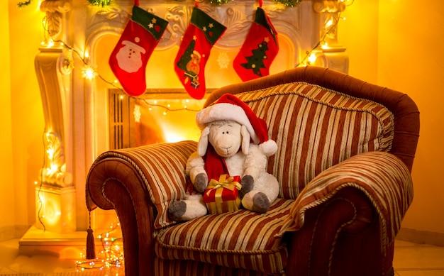 Interieurfoto van speelgoedlam zittend op een stoel bij de open haard met kerstmis