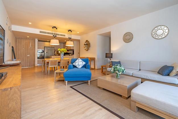 Interieurontwerp in villa, huis, huis, appartement en appartement met woonkamer met televisie, middentafel, kussen en open keuken en eetkamer