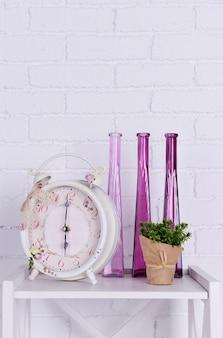 Interieurontwerp met wekker, plant en decoratieve vazen op tafelblad op witte bakstenen muur