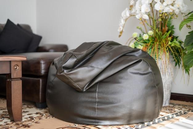 Interieurontwerp van huis, huis, villa en appartement voorzien van zwarte zitzak in woonkamer met tafel en kunstmatige plant