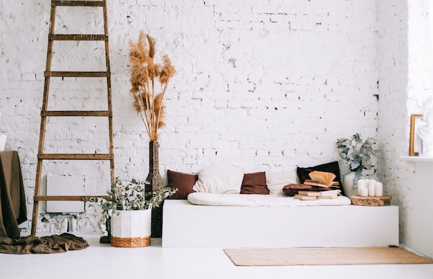 Interieurontwerp van lichte woonkamer met witte muren en bankbank met kussens