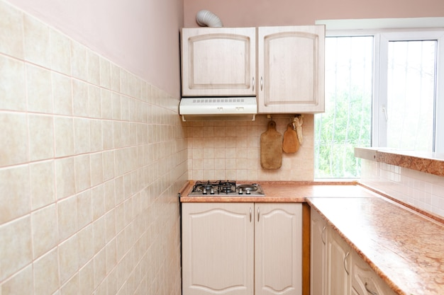 Interieurontwerp van moderne smalle slimme compacte keuken met wit eigentijds meubilair, beige keramische tegels op de muur, gasfornuis en raamweergave.
