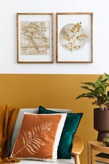 Interieurontwerp van moderne woonkamer met twee mock-up posterframes, elegante bank, plant, kussen en persoonlijke accessoires in stijlvolle huisstaging. honing geel concept.