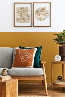 Interieurontwerp van moderne woonkamer met twee posterframes, elegante bank, plant, kussen en persoonlijke accessoires in een stijlvolle huisinrichting