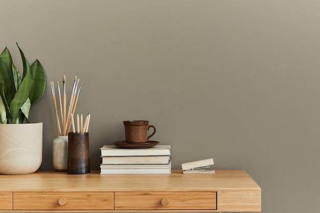 Interieurontwerp van neutraal bohemien woonkamerinterieur met stijlvol bureau, boek, beker, plant, kantoorbenodigdheden, klok, kopieerruimte, notities en persoonlijke accessoires.