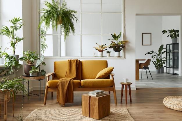 Interieurontwerp van scandinavische open ruimte met gele fluwelen bank, planten, meubels, boek, houten kubus en persoonlijke accessoires in stijlvolle huisstaging. sjabloon.
