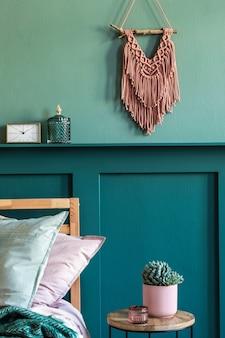 Interieurontwerp van slaapkamer met stijlvol meubilair, plant, macramé en elegante persoonlijke accessoires. plank boven bed. mooie roze en groene lakens, deken en kussen. home enscenering.