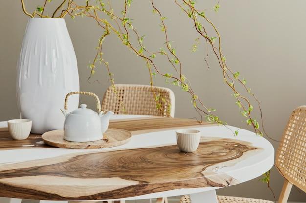 Interieurontwerp van stijlvol eetkamerinterieur met familie houten en epoxy tafel, rotan stoelen, bloemen in vaas en theepot met kopjes. details.