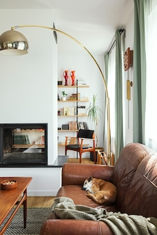 Interieurontwerp van stijlvol woonkamerinterieur met vintage meubels, thuiskantoorbibliotheek, open haard, lamp, decoratie en elegante persoonlijke accessoires in woondecoratie. sjabloon.