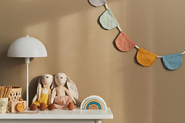 Interieurontwerp van stijlvolle kinderkamerruimte met witte plank, houten speelgoed, poppen, kinderaccessoires, witte lamp, gezellige decoratie en hangende katoenen vlaggen aan de beige muur. sjabloon.