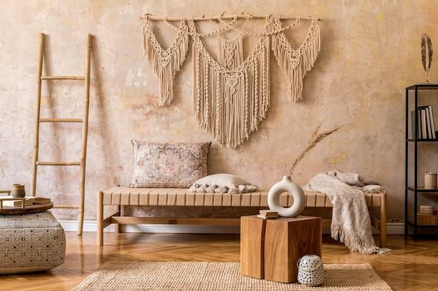Interieurontwerp van stijlvolle woonkamer met chaise longue, mooi macramé, rotan decoratie, planten, boek, plant, elegante persoonlijke accessoires in oosters concept van woondecoratie.