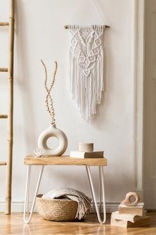 Interieurontwerp van woonkamer met stijlvolle gedroogde bloemen in vaas, houten ladder, plaid, wit macramé en persoonlijke accessoires in huisdecor.