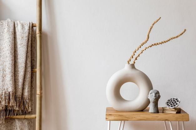 Interieurontwerp van woonkamer met stijlvolle gedroogde bloemen in vaas, houten ladder, plaid, witte muren en persoonlijke accessoires in huisdecor.