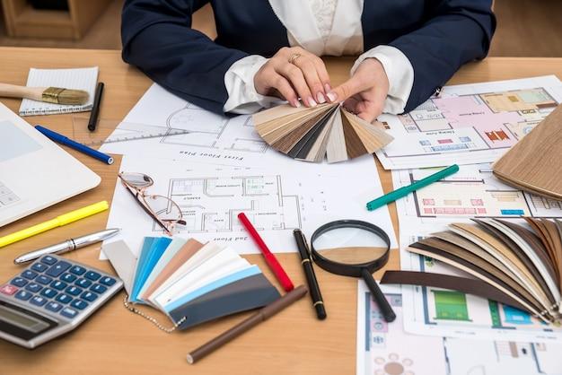 Interieurontwerper met kleurstaal en bouwtekeningen op kantoor