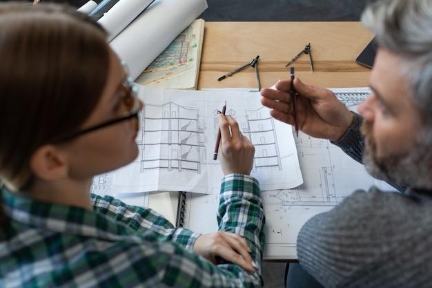 Interieurontwerpersteam dat op kantoor werkt met blauwdrukken en architectenapparatuur die onderhandelingen schetsen