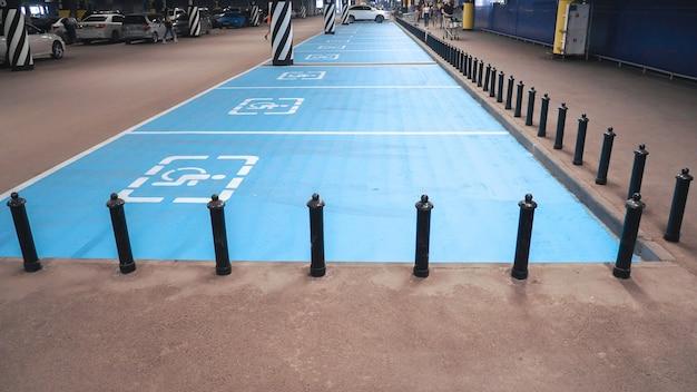 Internationaal gehandicapt symbool geschilderd in helder blauw op een winkelcentrumparkeerplaats.