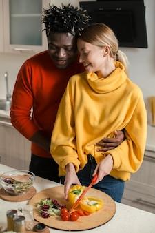 Internationaal koppel knuffelen met hun ogen dicht terwijl ze in de keuken zijn en vrouw groenten snijden