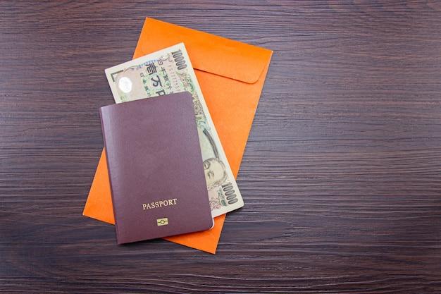 Internationaal paspoort en japanse bankbiljetten op oranje envelop aan tafel bruin donker hout.