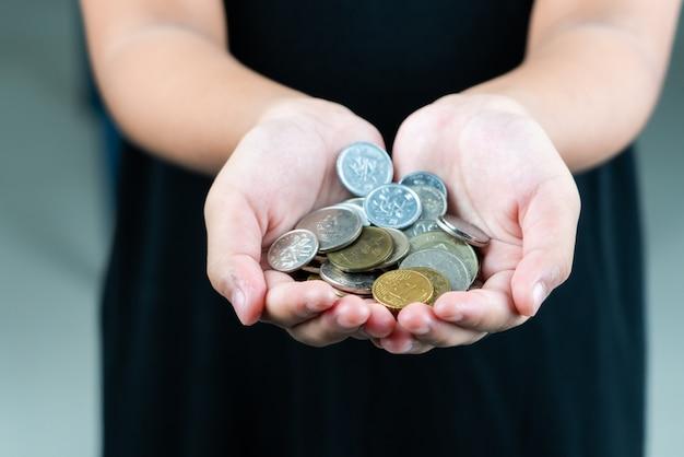 Internationaal schenkingsconcept - sluit omhoog van kinderenhanden houdend euro en internationale geldmuntstukken