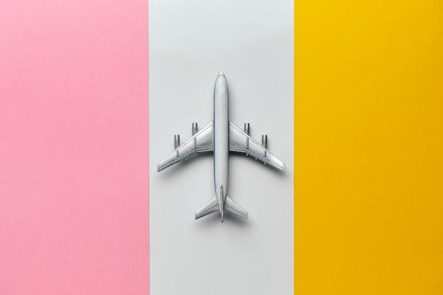 Internationaal vluchtenconcept met vliegtuigstuk speelgoed op een kleurrijke achtergrond.