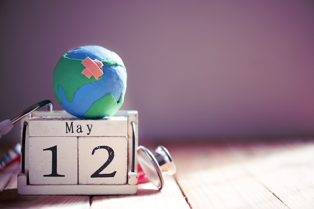 International nurses day, 12 mei handgemaakte globe met stethoscoop op houten tafel achtergrond