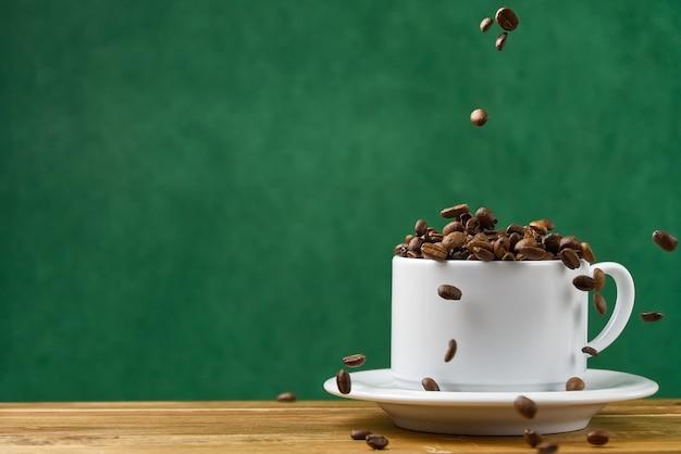 Internationale dag van koffie concept. close-up witte koffiekopje vol koffiebonen. koffiebonen vallen in de witte mok