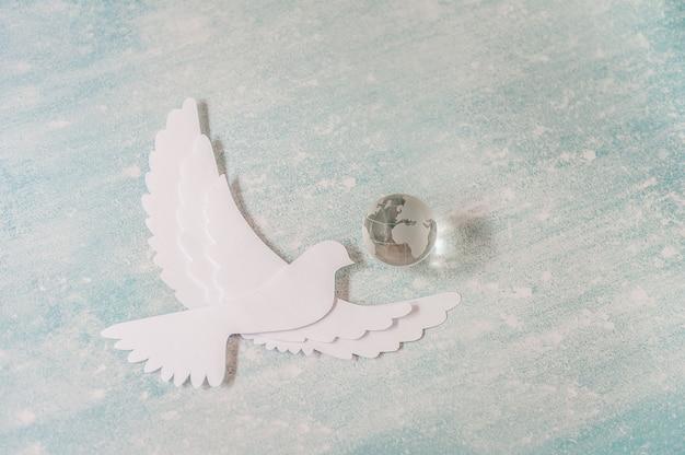 Internationale dag van vredesconcept: witte duif die op pastelkleur met glasbol vliegt.