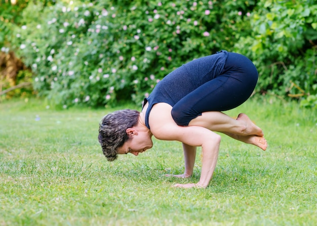 Internationale dag van yoga. vrouw die yoga buiten op groen gras op zonnige warme dag in park doet